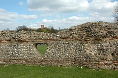 Mortared wall with stacked thick stone layers over thin red brick layers, with a triangular tunnel through
