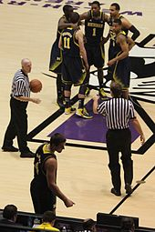 1b15b9323 Sixth man Mitch McGary checking into the Wolverines s Big Ten Conference  season opener at Welsh-Ryan Arena (starters in background clockwise from  front  ...