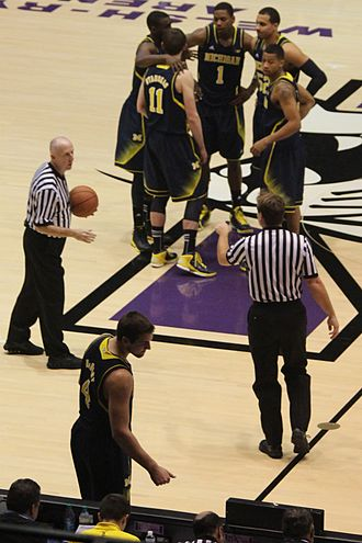 2012–13 Michigan Wolverines men's basketball team - Sixth man Mitch McGary checking into the Wolverines's Big Ten Conference season opener at Welsh-Ryan Arena (starters in background clockwise from front: Stauskas, Hardaway, Jr., Robinson III, Morgan, and Burke)