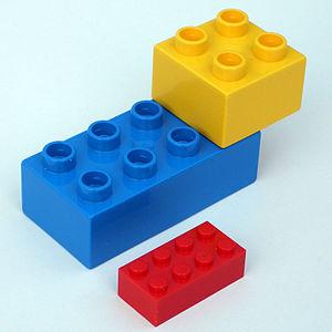 Lego Duplo - Duplo bricks alongside a smaller red regular-sized Lego brick