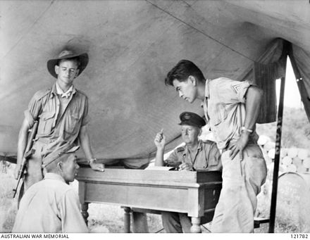 26 October 1945, Sandakan, North Borneo. During the investigation into Sandakan Death Marches and other incidents, Sergeant Hosotani Naoji (left, seated), a member of the Kempeitai unit at Sandakan, is interrogated by Squadron Leader F.G. Birchall (second right) of the Royal Australian Air Force, and Sergeant Mamo (right), a Nisei member of the U.S. Army/Allied Translator and Interpreter Service. Naoji confessed to shooting two Australian POWs and five ethnic Chinese civilians. AWM 121782 sandakan.jpg