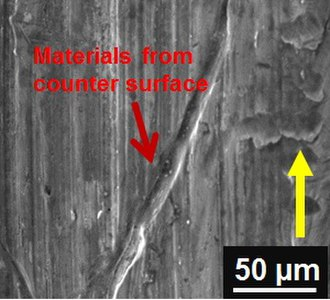 Wear - SEM micrograph of adhesive wear (transferred materials) on 52100 steel sample sliding against Al alloy. (Yellow arrow indicate sliding direction)