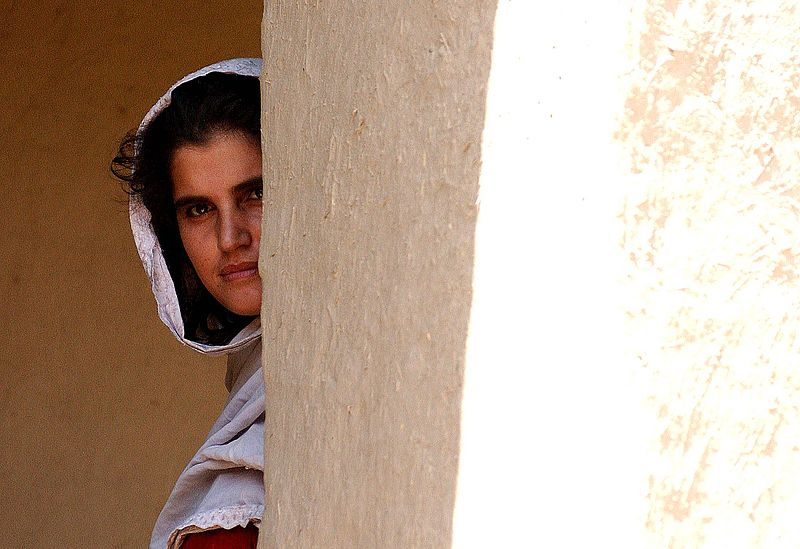 An Afghan woman peers around a corner.