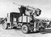 An Italian 90-53 gun on a truck mounting joining the rows of derelict Axis vehicles and equipment jettisoned by Rommel's army.jpg