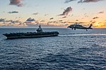 An MH-60S Sea Hawk flies near the USS Ronald Reagan during search-and-rescue training. (29630444444).jpg