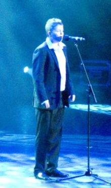 Johnston, a thick-set, teenage boy with short, spiked hair stands on stage and sings into a microphone. He is wearing a dark blazer, dark trousers and black shoes, with a white shirt and no tie.