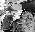 Anne Keys of the Women's Land Army reverses a tractor out of a shed during her training at the Northampton Institute of Agriculture near Moulton in 1942. D8823.jpg