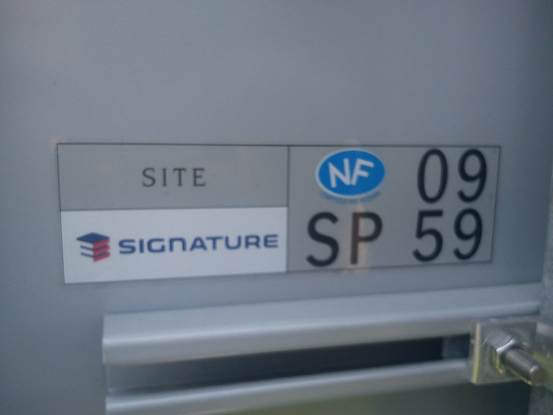 Étiquette à l'arrière d'un panneau de signalisation portant la mention: NF SP 09 59.