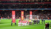 A line of people on a field, behind them are three red banners.UEFA Champions League quarter-final