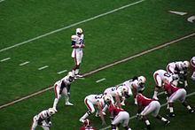 A quarterback is behind the offensive line preparing to take a snap.