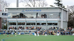A grey coloured function centre with glass windows. Spectators and an interchange bench are in front of the structure.