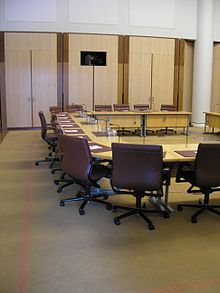 A meeting room containing a large horseshoe-shaped desk, with red leather office chairs surrounding its outside edge, a microphone mounted in the desk in front of each chair