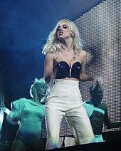 O femeie cu părul blond și un microfon până la gură