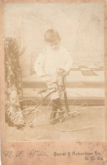 Boy with tricycle by Wilde of New Orleans USA.png