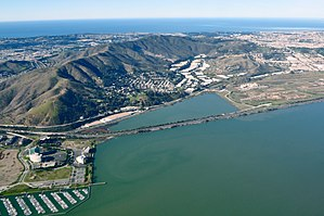 Brisbane Baylands development - This picture, facing west, shows the city of Brisbane, which is sheltered by the prominent San Bruno Mountain rising in the background. The proposed Brisbane Baylands includes the land between the railroad tracks and highway 101 (closer to the camera) north of the triangular Brisbane Lagoon.