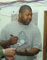 Candid waist-up photograph of Cox wearing a grey t-shirt and apparently signing an autograph