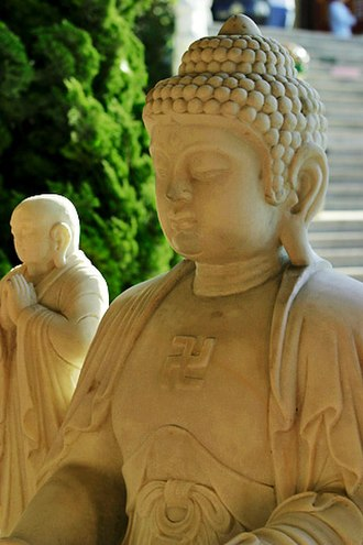 Schools of Buddhism - An image of Gautama Buddha with a swastika, a traditional Buddhist symbol of infinity, on his chest. Ananda, the Buddha's disciple, appears in the background.  This statue is from Hsi Lai Temple.