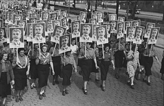 Stalin's cult of personality - Female members of the FDJ carry Stalin's pictures in the 3rd World Festival of Youth and Students in East Berlin.