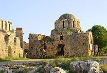 Развалины небольшой каменной куполообразной структуры, построенной в византийском стиле с высокими окнами.  Злаки растут на втором уровне, как и деревья за ним.
