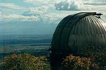 Photo en couleur. Un objet semi-sphérique se découpe devant un paysage naturel composé de plantes et d'un ciel nuageux.