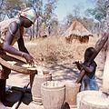 COLLECTIE TROPENMUSEUM Een vrouw voegt water toe tegen het stuiven van te stampen mais omgeving van Kasempa TMnr 20039222.jpg