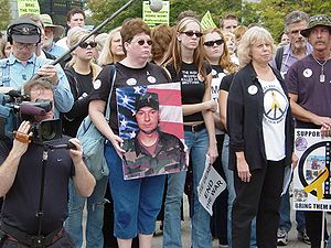 Friends and family of Cindy Sheehan hold a photo of Casey Sheehan at an anti-war demonstration in Arlington, Virginia on October 2, 2004.