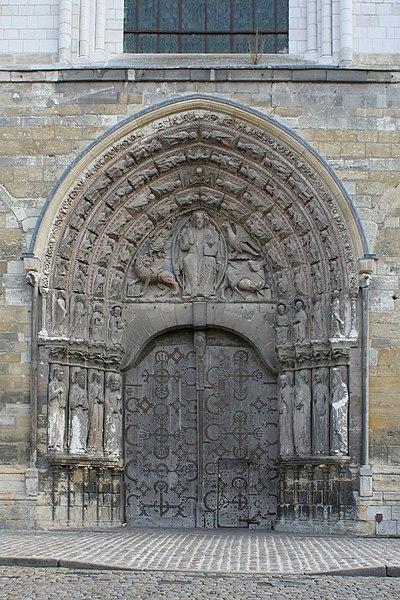 Portail occidental de la cathédrale d'Angers. Statues-colonnes dans les ébrasements, personnages (anges, musiciens) dans les voussures de l'archivolte, Christ en mandorle entouré du symbole des quatre évangélistes tétramorphe dans le tympan. Traces de polychromie. Linteau en arc en doucines affrontées. Porte à deux vantaux à pentures et fausses-pentures, guichet dans le vantail de droite.