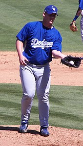 A man in a blue baseball jersey, cap, and gray pants catches a baseball in a glove on his left hand.