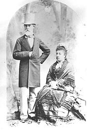 An old man in a top hat with a white beard stands next to a sitting woman in a decorative dress