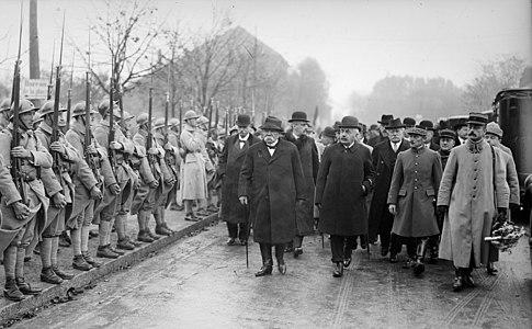 Zwart-witfoto van een stoet mannen in burgerkleding en militair uniform die militaire troepen bekijken