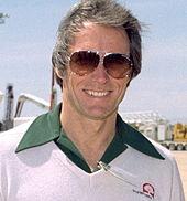 Photographie de Clint Eastwood en 1981. Il porte des lunettes de soleil, a les cheveux grisonnants et porte une chemise surmontée d'un pull