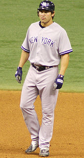 "A man in a gray baseball uniform with ""NEW YORK"" on the chest and a dark batting helmet stands in the infield dirt of a baseball diamond."