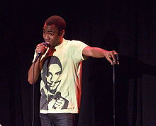Donald Glover standing onstage holding a microphone and wearing a t-shirt of Alfonso Ribeiro