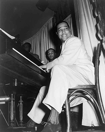 Duke Ellington straddled the big band and bebop genres. Ellington extensively used the blues form. Duke Ellington at the Hurricane Club 1943.jpg
