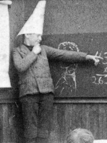 A young boy wearing a dunce cap in class, from a staged photo c.1906