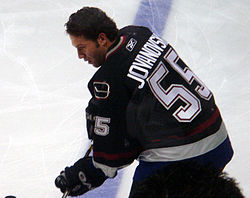 A Caucasian hockey player looking down at the ice while slightly crouched over. He is not wearing a helmet and is dressed in a black jersey with blue and maroon trim.