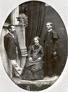 Three people: from left to right, a moustachioed gentleman of Mediterranean appearance, an older woman sitting on a chair, and a Catholic priest.