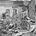 Een Indonesiër met een fiets in een ruïne van een winkel in Bandoeng, Bestanddeelnr 255-8321.jpg