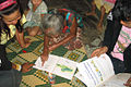 Elderly Lao woman reading.jpg