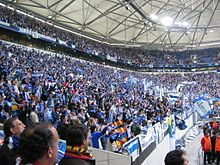 A pitch level perspective of the corner section of a stadium filled with people holding blue scarfs and waving blue-and-white flags.