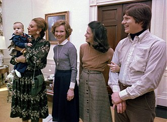 Farah Pahlavi, Empress of Iran, holds Jimmy Carter IV while Rosalynn Carter, Caron Carter and Chip Carter watch, January 1978. Farah Pahlavi and Rosalynn Carter (cropped and retouched).jpg
