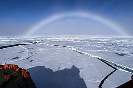 A multi-coloured arc emerges from fog above a frozen see. The picture is taken from an icebreaker, part of its bow and shadow being visible in the front left corner of the picture.
