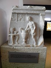 Framentuary votive relief representing a youth ladling wine for a krater and a round table with vases, from the Agora, end of 4th c. BC, Archaeological Museum, Pella (7065345633).jpg