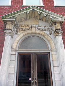 An arched stone entrance on a brick background, with smooth columns on either side and metal-framed glass double doors topped by a round-arched transom with keystone and a stone pediment