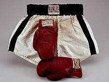 .Deux gants de boxe rouges devant un short de boxe noir et blanc.