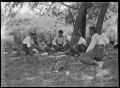 Group of men at rest, playing cards on the grass under a tree, on the Mendip Hills sheep farm. ATLIB 284081.png