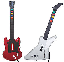 A photograph of two guitar-shaped video game controllers side-by-side, the left one red and the right one white all on a solid, white background
