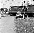 HUA-167633-De spoorwegovergang in de spoorlijn Lage Zwaluwe-Breda, nabij Zevenbergschenhoek, met een voorbijrijdende trein en links op de achtergrond de wachterswoning nr. 1 aan de spoorlijn Lage Zwaluwe - 's-Hertogenbosch.jpg