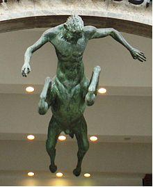 Statuia unui cal-om: capul și bustul unui om, corp, membre și coadă de cal, văzute de jos.