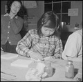 Heart Mountain Relocation Center, Heart Mountain, Wyoming. A young enthusiast working on a pair of . . . - NARA - 539232.tif